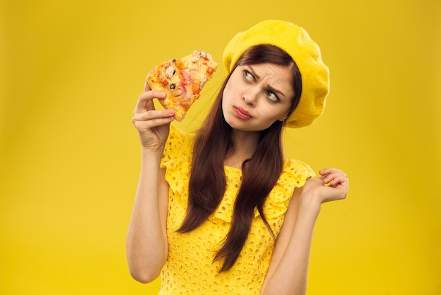Young woman in yellow clothes eats pizza