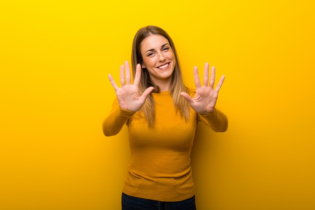 Young woman on on yellow  counting ten with fingers