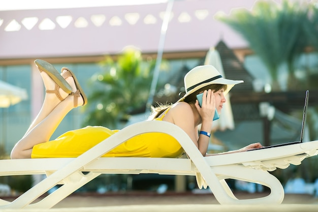 Young woman in yellow dress is laying on beach chair working on computer laptop having conversation on mobile phone in summer resort. doing studies while travelling concept.