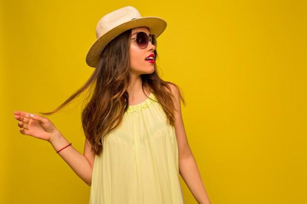 Giovane donna in abito giallo con cappello e occhiali da sole