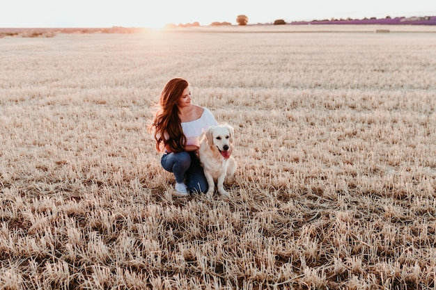 Young woman in a yellow field with her golden retriever dog at sunset. pets outdoors