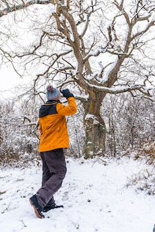 A young woman in a yellow jacket under a beautiful giant tree frozen by the winter cold. snow in the town of opakua near vitoria