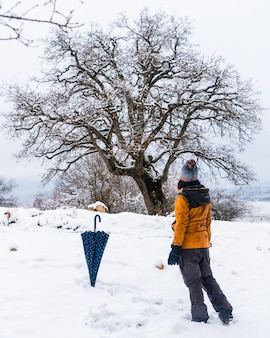 A young woman in a yellow jacket looking at a beautiful tree in the snow. snow in the town of opakua near vitoria in araba