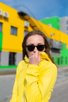 A young woman in a yellow jacket and sungalsses with bright colors buildings in the background