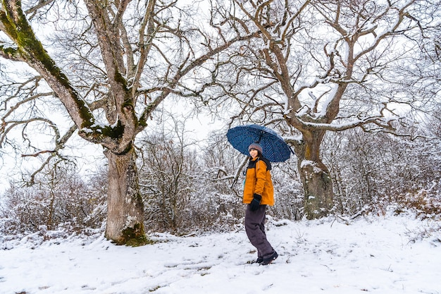 A young woman in a yellow jacket and an umbrella playing with the snow on a tree branch. snow in the town of opakua near vitoria