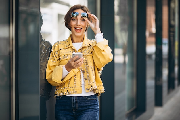 Young woman in yellow jacket using phone outside in the street