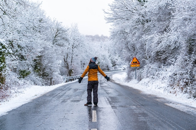 A young woman in a yellow jacket walking along an icy road and denied trees. snow in the town of opakua near vitoria in araba