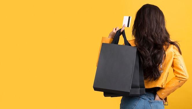 Giovane donna nello spazio giallo della copia del rivestimento di pelle