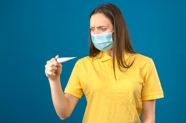 Giovane donna in camicia di polo gialla e maschera protettiva medica che esamina termometro nel panico su fondo blu isolato