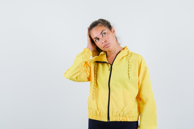 Young woman in yellow raincoat adjusting her hair while looking aside and looking focused