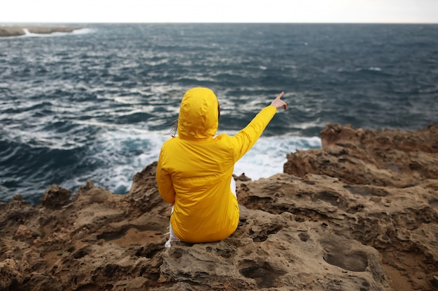 Young woman in yellow raincoat is sitting on the cliff looking on big waves of the sea while enjoying beautiful sea landscape in rainy day on the rock beach in cloudy spring weather