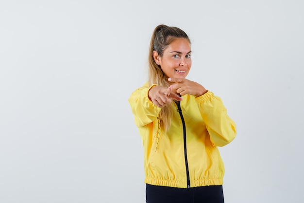 Young woman in yellow raincoat pointing at front and looking joyful