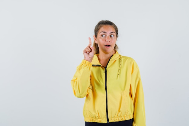 Young woman in yellow raincoat pointing up while looking aside and looking careful