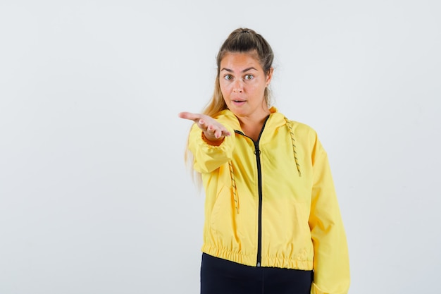 Young woman in yellow raincoat raising hand for showing something and looking focused