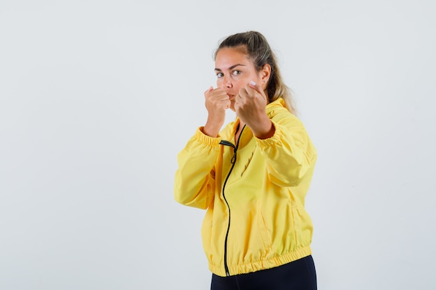 Young woman in yellow raincoat showing her fists and looking powerful