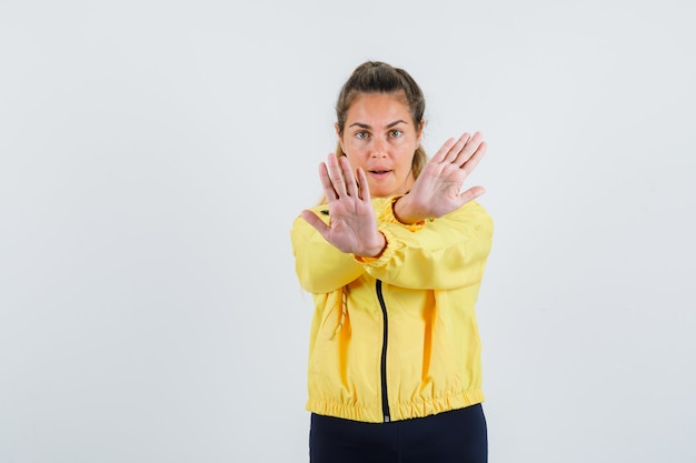 Young woman in yellow raincoat showing stop gesture with reverse hands and looking serious