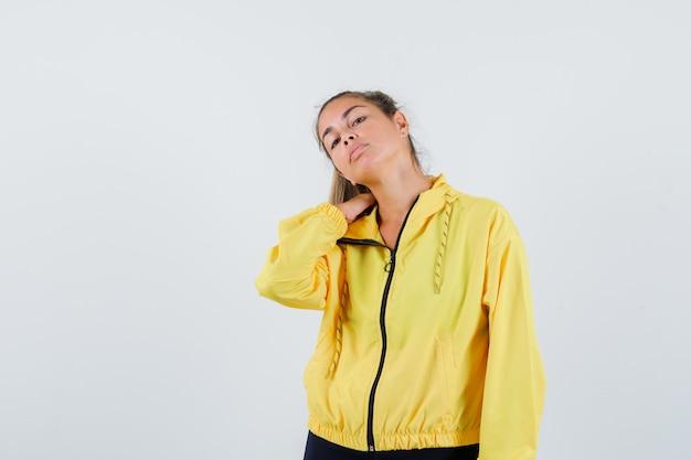 Giovane donna in impermeabile giallo che soffre di dolore al collo e sembra turbata