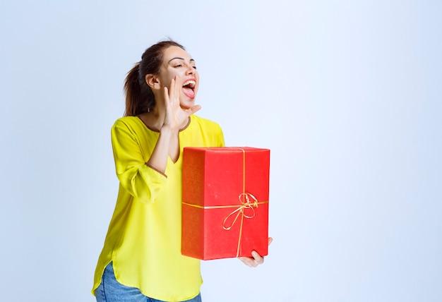 Giovane donna in camicia gialla che chiama o invita qualcuno a presentare una confezione regalo rossa