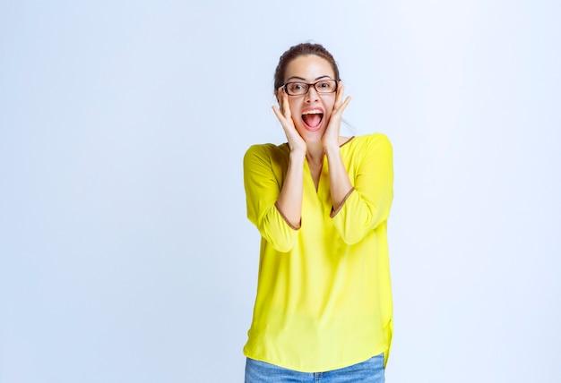 Giovane donna in camicia gialla che si sente positiva e ride