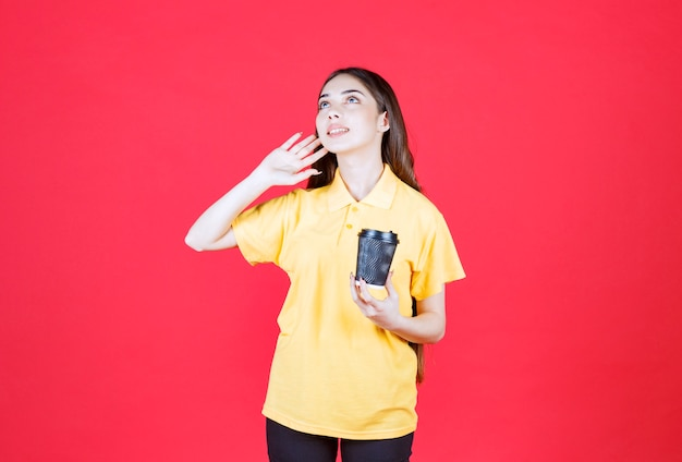 Young woman in yellow shirt holding a black disposable coffee cup and calling someone