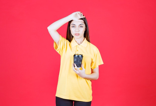 Giovane donna in camicia gialla che tiene una tazza di caffè usa e getta nera e sembra stanca e assonnata