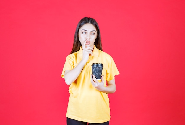 Young woman in yellow shirt holding a black disposable coffee cup, thinking and having a good idea