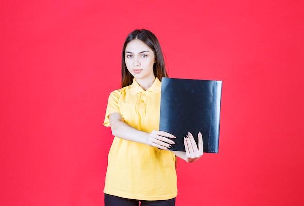 Giovane donna in camicia gialla che tiene una cartella nera