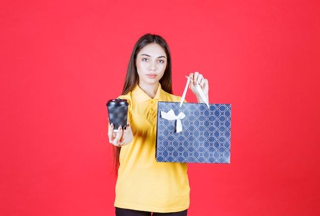 Giovane donna in camicia gialla che tiene in mano una borsa della spesa blu e una tazza di bevanda nera usa e getta