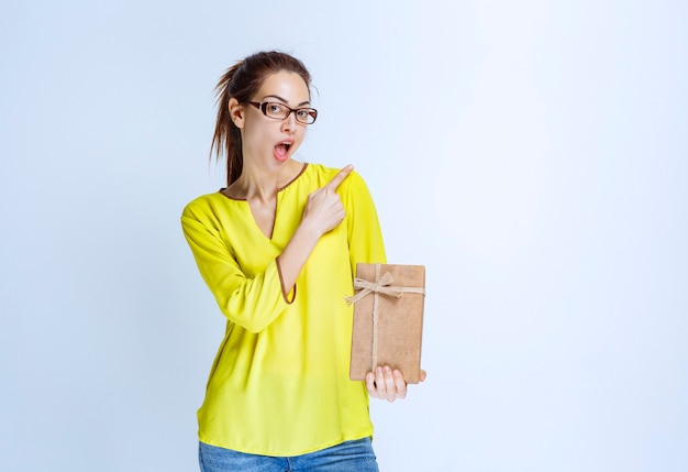 Giovane donna in camicia gialla che tiene in mano una scatola regalo di cartone e indica qualcuno sulla destra