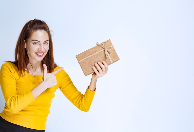 Giovane donna in camicia gialla che tiene in mano una scatola regalo di cartone e mostra un segno positivo con la mano