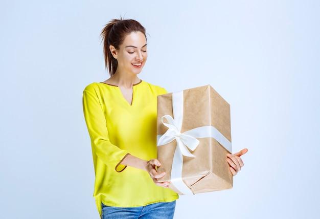 Giovane donna in camicia gialla che tiene in mano una scatola regalo di cartone, sorride e si sente positiva