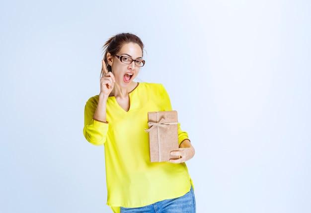 Giovane donna in camicia gialla che tiene una scatola regalo di cartone