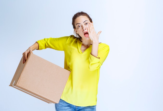 Young woman in yellow shirt holding a cardboard parcel and loks thoughtful