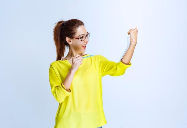 Giovane donna in camicia gialla che tiene il foglio dell'esame e pensa mentre tiene in mano una penna