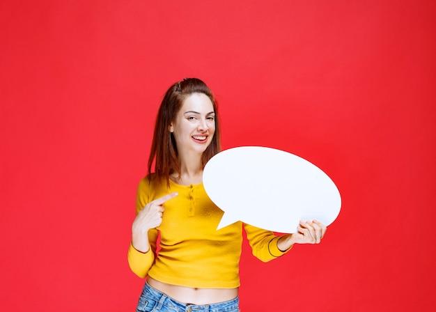 Giovane donna in camicia gialla che tiene un pannello informativo ovale