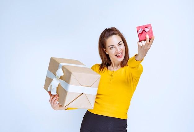 Giovane donna in camicia gialla che tiene in mano una scatola regalo rossa e una di cartone