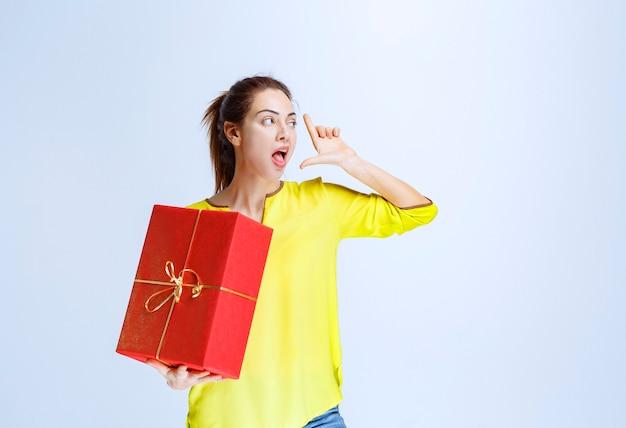 Giovane donna in camicia gialla con in mano una confezione regalo rossa data al giorno di san valentino
