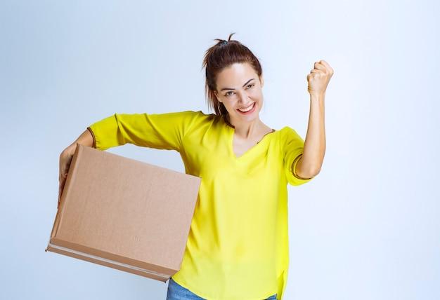 La giovane donna in camicia gialla ha ricevuto il suo carico e mostra il segno di divertimento