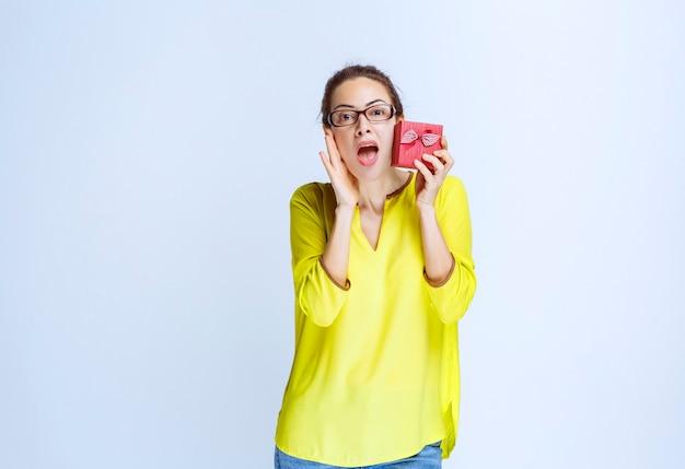 Giovane donna in camicia gialla che mostra la sua confezione regalo rossa e sembra sorpresa
