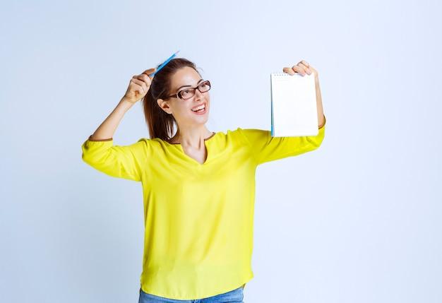 Giovane donna in maglietta gialla che mostra i risultati del quiz e gli errori su di esso