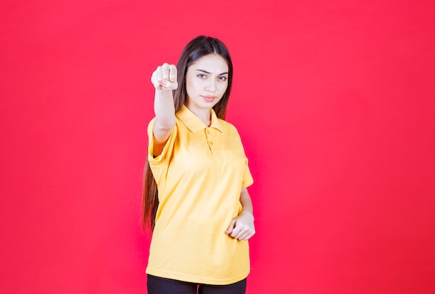 Young woman in yellow shirt standing on red wall and showing positive hand sign