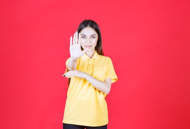 Giovane donna in camicia gialla in piedi sul muro rosso e ferma qualcosa