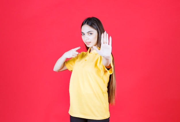 Young woman in yellow shirt standing on red wall and stopping something