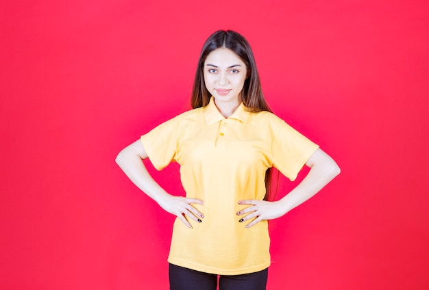 Young woman in yellow shirt standing on red wall