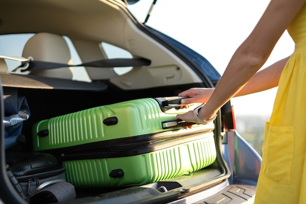 Young woman in yellow summer dress taking green suitcase from car trunk