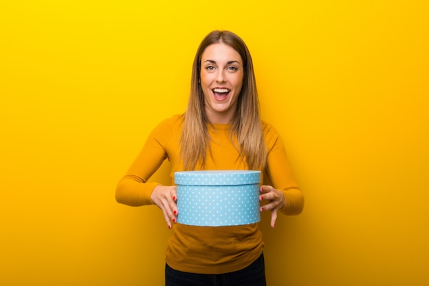 Young woman on yellow  surprised because has been given a gift