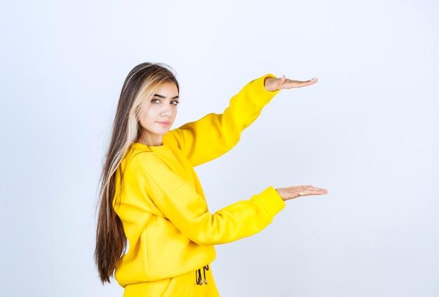 Giovane donna in pantaloni della tuta gialli e felpa con cappuccio in piedi sul muro bianco