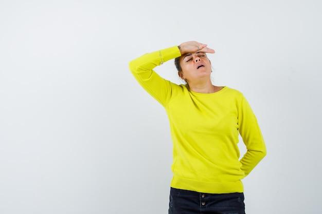 Giovane donna in maglione giallo e pantaloni neri che mette la mano sulla fronte, tiene la mano dietro la vita e sembra esausta