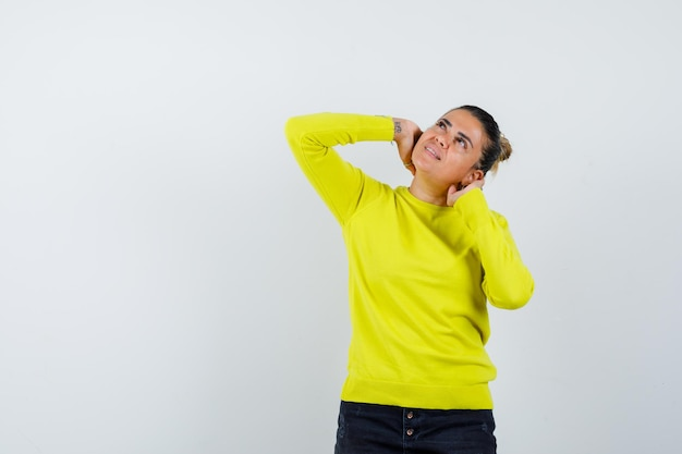 Young woman in yellow sweater and black pants putting hands behind neck, looking above and looking pensive