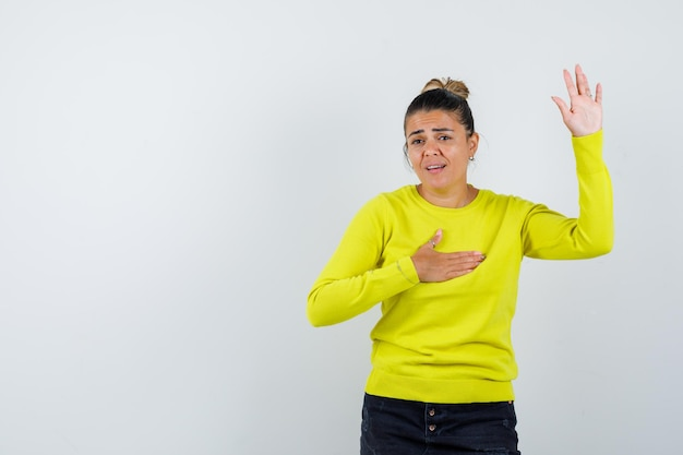 Young woman in yellow sweater and black pants raising hand and holding hand on chest and looking excited